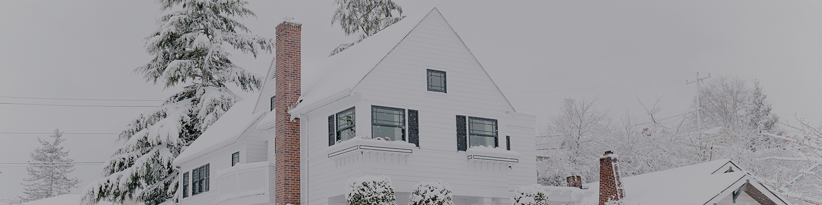 Colonial House covered in snow during a blizzard can cause ice dams