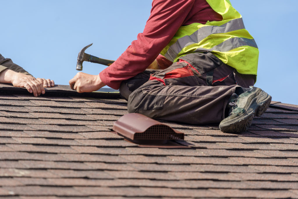 Image of roofer nailing down a roof cap on a multifamily home